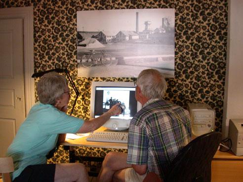 Ulla och Elfon Finnström letar bland Yngve Öhrbergs bilder. På väggen ser man en av Hans Åströms Svartviksmotiv. Bild från förra biblioteket i herrgårdens norra flygel. Foto: Kenth Wiklund, 2002.